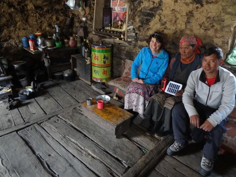 Una caminante, una sherpa y un portero descansan en una tradicional casa sherpa